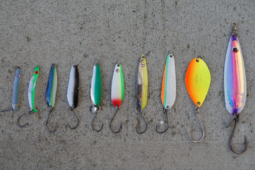 A good selection of trout spoons. From left to right, Wee-G in Gold Nugget, Coho Killer in Irish Cream, Kingfisher in Herring Aid, Gypsy in Paddy Wagon, Razorback in Killy Magee, G-Force in No Bananas, Skinny-G in Nickel Chartreuse, G-Force in Outfitter, FST in Fire Orange Chartreuse, Titan in Kinetic Purple.