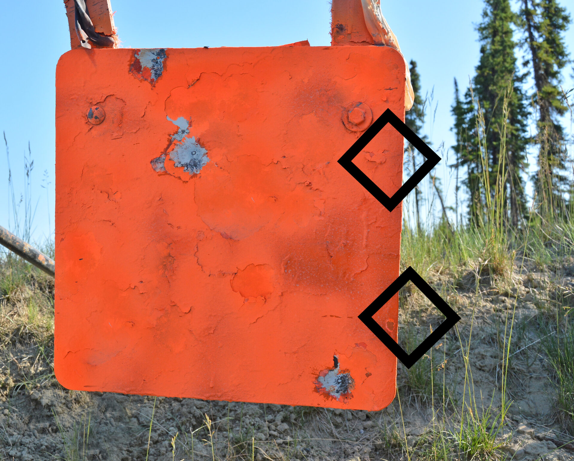 Laser rangefinders should be tested for reticle/beam alignment by ranging near all four edges of a rectangular target. Here, the top reticle placement should read the target distance, while the bottom placement should read the area behind the target. Repeat for all four sides.